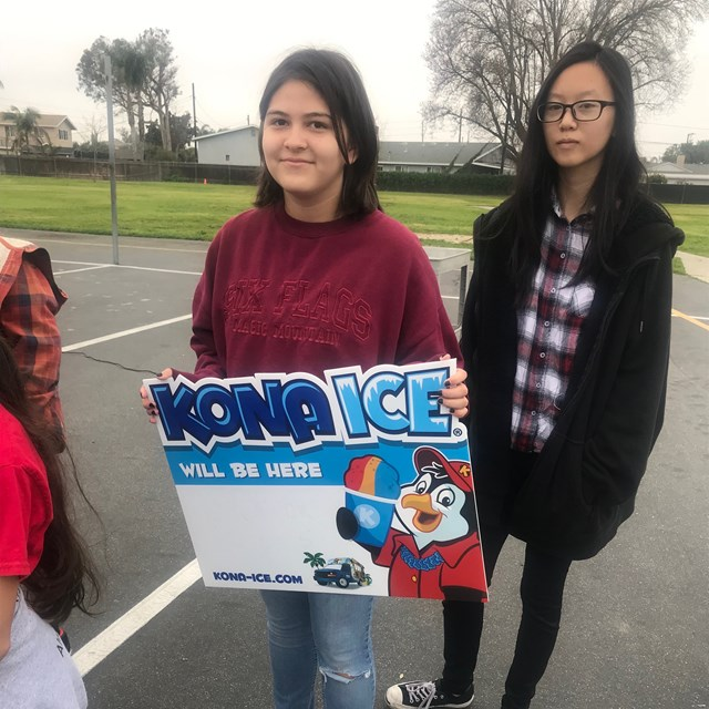 Student holding a Kona Ice sign.