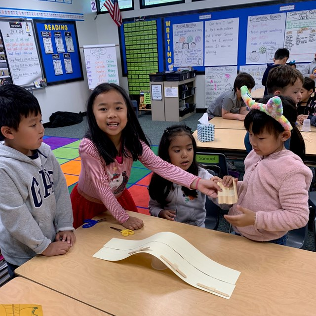 Students building a bridge out of popsicle sticks, a cup, and tape.